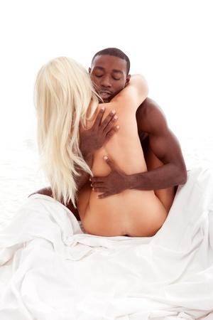 Heterosexual interracial couple of Caucasian blond woman and Ethnic black African American man embracing in sensual hug
