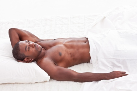 Young handsome Athletic muscular ethnic black Afro-American man resting in bed photo