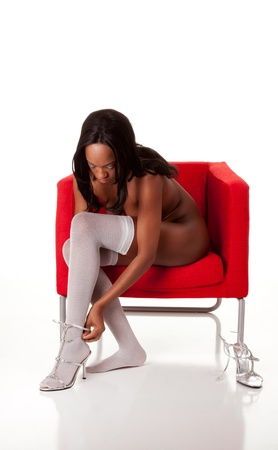afro american nude: Beautiful nude slim slender black Afro-American female stripper putting on stockings and high heel shoes sitting on chair