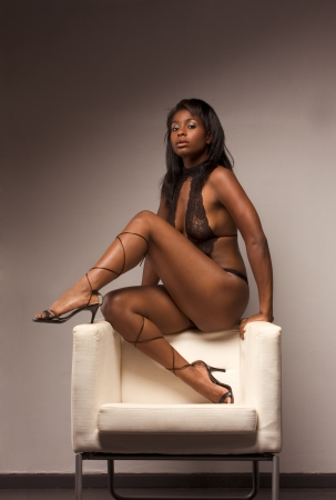 Portrait of young voluptuous sensual Hispanic woman in brown lingerie sitting on top of armchair photo