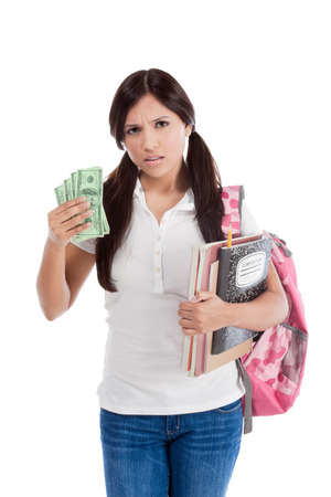 Ethnic Hispanic college student with notebook and backpack holds pile 100 (one hundred) dollar bills happy getting money frustrated by exuberant raising tuition cost and unaffordable education forcing into debt Banque d'images