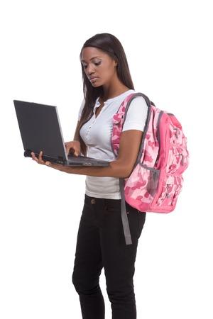brunnet: la educaci�n serie plantilla - Friendly �tnico negro mujer estudiante de la escuela de alta escribiendo en la computadora port�til Foto de archivo
