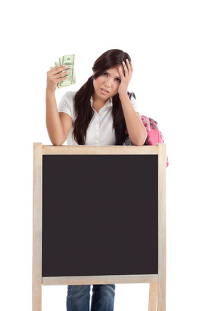 Ethnic Hispanic college student with notebook and backpack holds pile 100 (one hundred) dollar bills happy getting money frustrated by exuberant raising tuition cost and unaffordable education forcing into debt Stock Photo - 25193234
