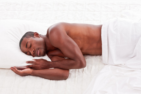 Young handsome Athletic muscular ethnic black Afro-American man resting in bed