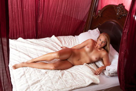 Young nude blond Caucasian woman on bed Stock Photo