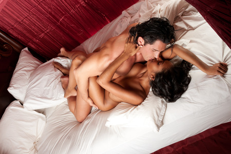 Lovers - Interracial sensual couple making love in bed Stock Photo