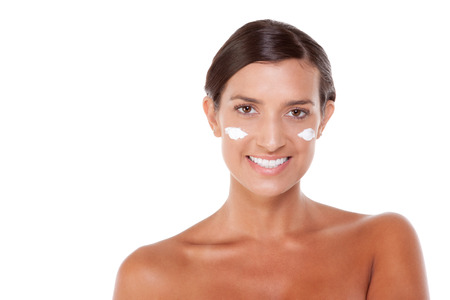 slicked: Young Caucasian woman putting cream on her face Stock Photo