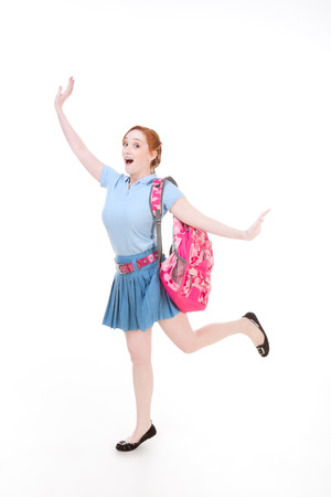 education back to school series - Friendly Caucasian woman high school student with backpack in uniform skirt jumping in excitement photo
