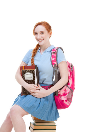 Young Caucasian female college student with backpack in skirt sitting on huge pile of educational books from library