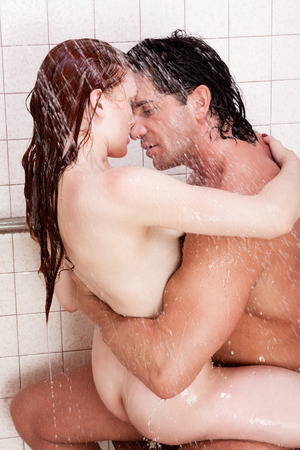 Loving affectionate nude young heterosexual couple in affectionate sensual kiss after taking shower. Mid adult Caucasian men in late 30s and young Caucasian redhead woman in early 20s photo