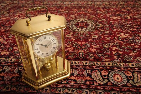 Antique clock on a Persian rug Stock Photo