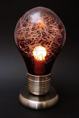 A large decorative desk lamp shaped like a lightbulb  on black background.