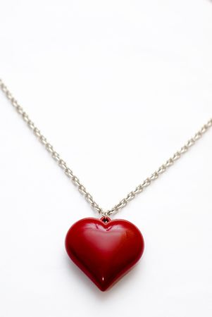 A silver necklace with a large heart shaped pendant