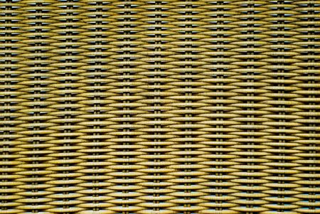 A closeup of a chair handmade from weaved rattan, like bamboo.