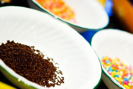 A bowl of chocolate sprinkles with star-shaped sweets in background. Ingredients for making homemade cookies. Stock Photo