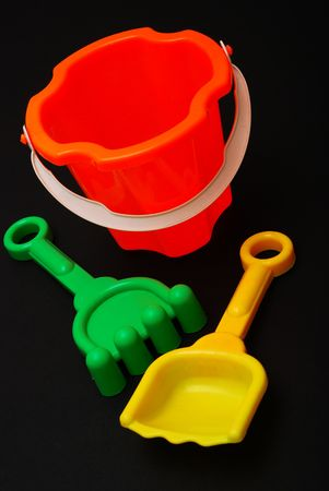 Plastic beach toys on black background Stock Photo