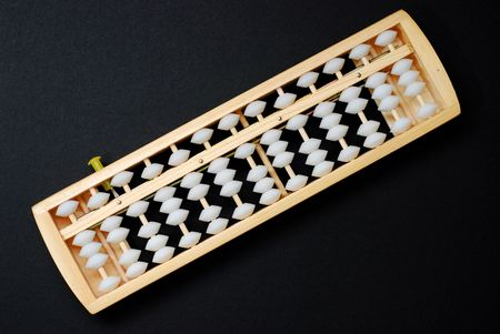 An abacus, a traditional calculating device on black background