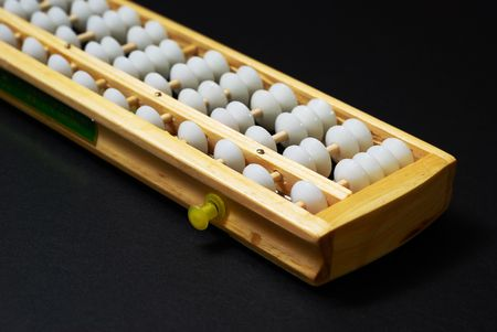 Closeup of an abacus, a traditional calculating device on black background