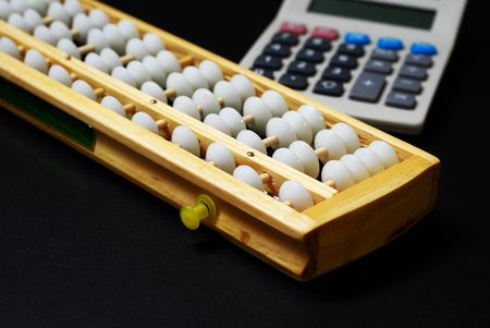 A traditional abacus and a modern calculator on black background Stock Photo