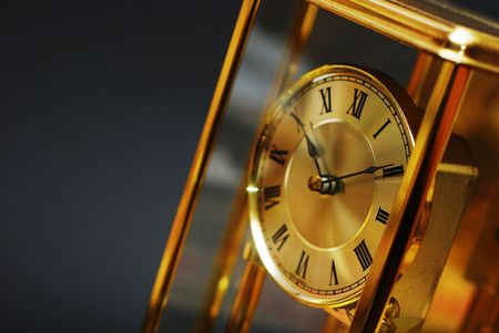Antique gold clock with Roman numerals on black background
