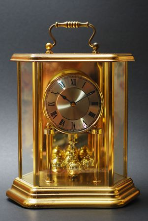 An antique gold clock with Roman numerals on black background