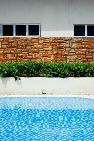A swimming pool with a brick wall and some plants at the edge Stock Photo