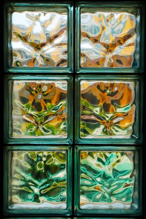 Closeup of glass blocks on office wall with colourful pattern
