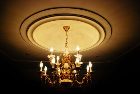 A large chandelier with candle shaped lights in a dark room