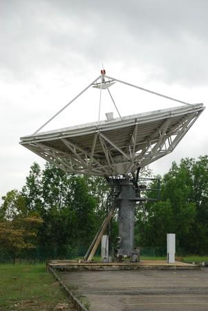 Satellite dish in carpark, pointing to sky Stock Photo