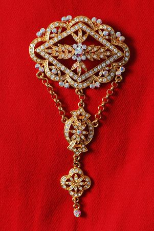Gold brooch with many diamonds and gems, on red cloth background