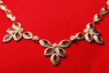 Gold necklace with red ruby and small gems like diamonds