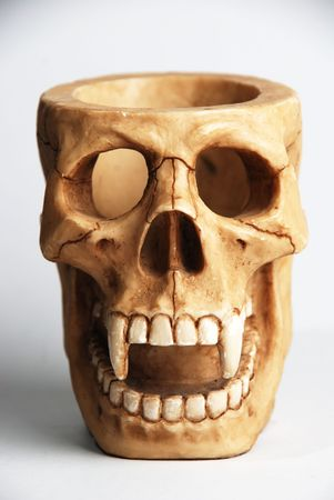 A stationary holder shaped like a skull with large fangs and open top head