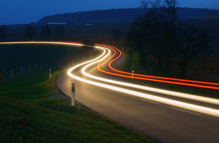 travel background: Car trails on the night road in the hilly countryside.