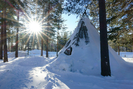 Winter polar forest landscape with eskimo tent and sun in the Sweden.