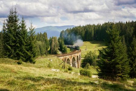 Old historic railway viaduct bridge in Ukraine with the steam train.