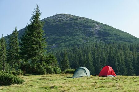 Summer landscape with camping tents on mountain valley and hills mountains peak. Stok Fotoğraf