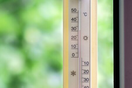 The thermometer outside the window shows high hot temperature. Stok Fotoğraf