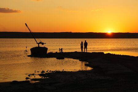 Landscape with water, old boat and couple silhouette at sunset. Lifestyle concept.