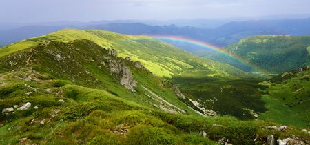Panoramic view of mountain landscape with rainbow.
