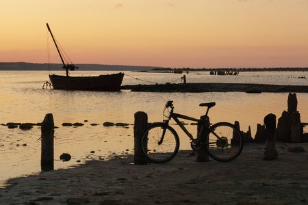 Landscape with sea estuary, old boat and bicicle at sunset. Lifestyle concept.
