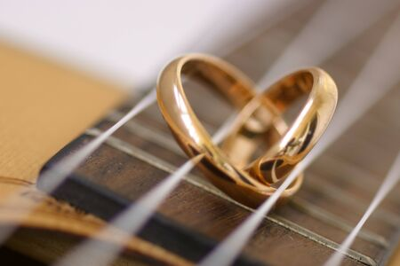 Wedding ring in a heart shape laying on ukulele guitar strings.