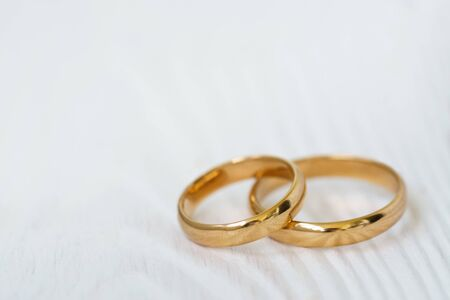 Wedding background with two rings on white wood with copy space.