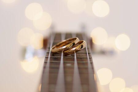 Wedding rings laying on ukulele guitar strings. Stok Fotoğraf
