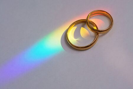 Two wedding rings with rainbow light.