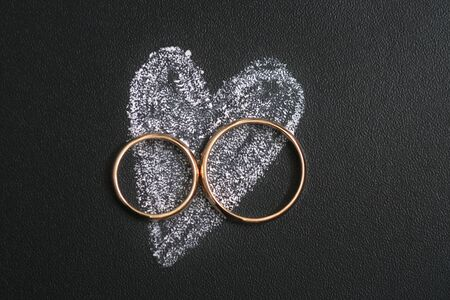 Wedding rings and heart drawing with calk on calkboard. Husband and wife or groom and bride, married couple in love concept. Stok Fotoğraf
