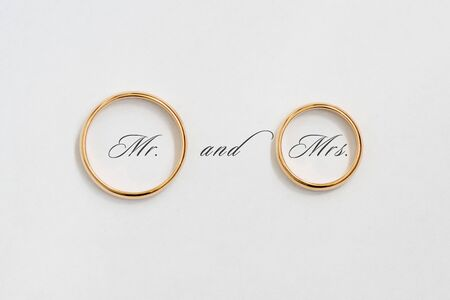Golden wedding rings on white paper.