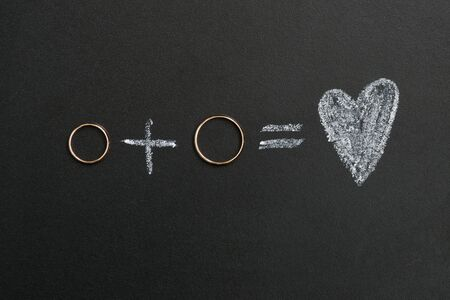 Wedding rings and plus and heart drawing with calk on calkboard. Husband and wife or groom and bride, married couple concept.