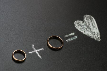 Trauringe und Plus- und Herzzeichnung mit Kalk auf Tafel. Ehemann und Ehefrau oder Bräutigam und Braut, Ehepaarkonzept.