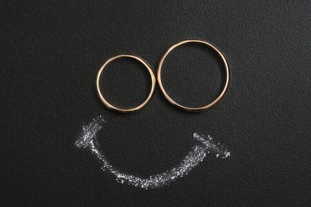 Wedding rings and smile drawing with calk on calkboard. Husband and wife or groom and bride, happy married couple concept.