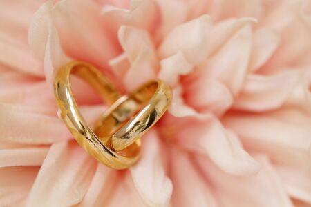 Wedding rings in heart shape on pink dahlia flower.